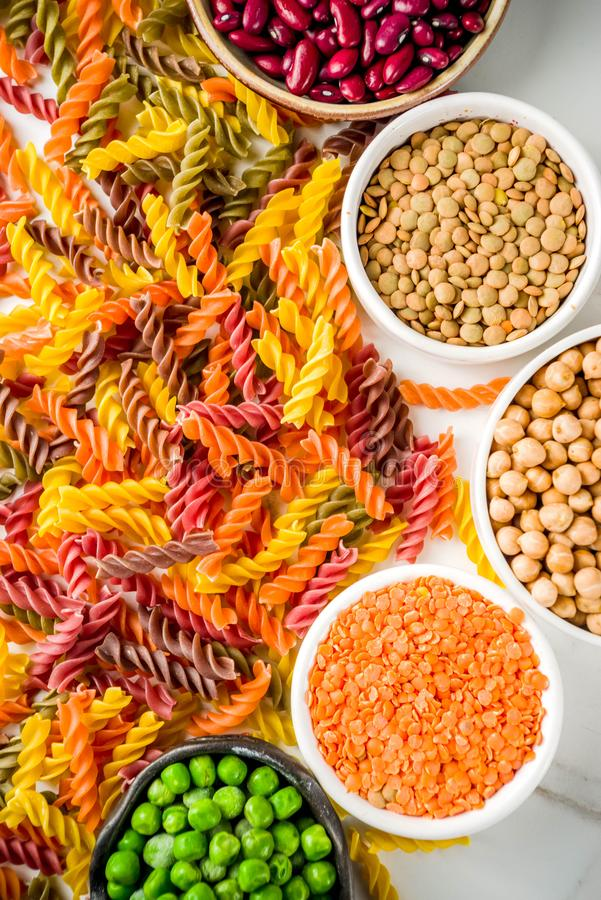 Trend healthy food, vegan diet concept. Multi colored legume pasta with raw beans. Beans, chickpeas, green peas, lentils. Copy royalty free stock photography