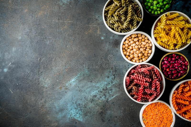 Trend healthy food, vegan diet concept. Multi colored legume pasta with raw beans. Beans, chickpeas, green peas, lentils. Copy. Space top view stock photos