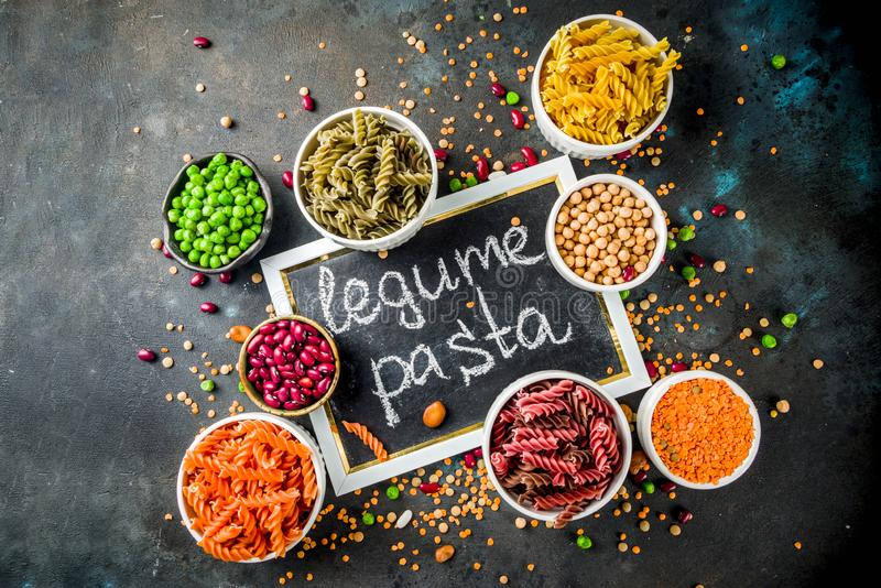 Trend healthy food, vegan diet concept. Multi colored legume pasta with raw beans. Beans, chickpeas, green peas, lentils. Copy. Space top view stock photo