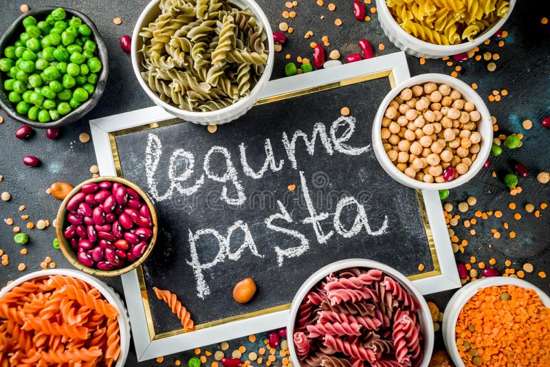 Trend healthy food, vegan diet concept. Multi colored legume pasta with raw beans. Beans, chickpeas, green peas, lentils. Copy. Space top view royalty free stock images