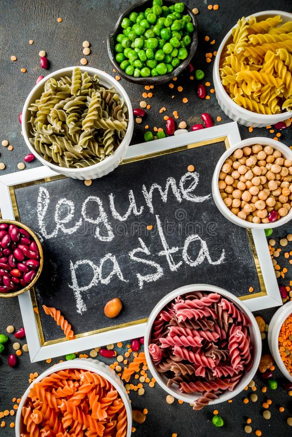 Trend healthy food, vegan diet concept. Multi colored legume pasta with raw beans. Beans, chickpeas, green peas, lentils. Copy. Space top view royalty free stock image