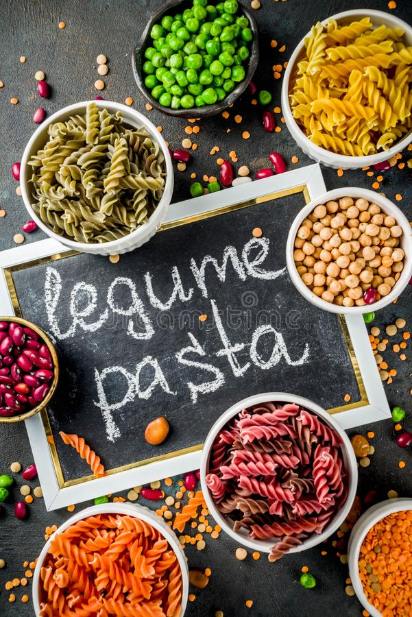 Trend healthy food, vegan diet concept. Multi colored legume pasta with raw beans. Beans, chickpeas, green peas, lentils. Copy. Space top view royalty free stock photos