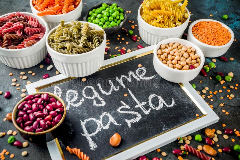 Trend healthy food, vegan diet concept. Multi colored legume pasta with raw beans. Beans, chickpeas, green peas, lentils. Copy. Space top view royalty free stock photo