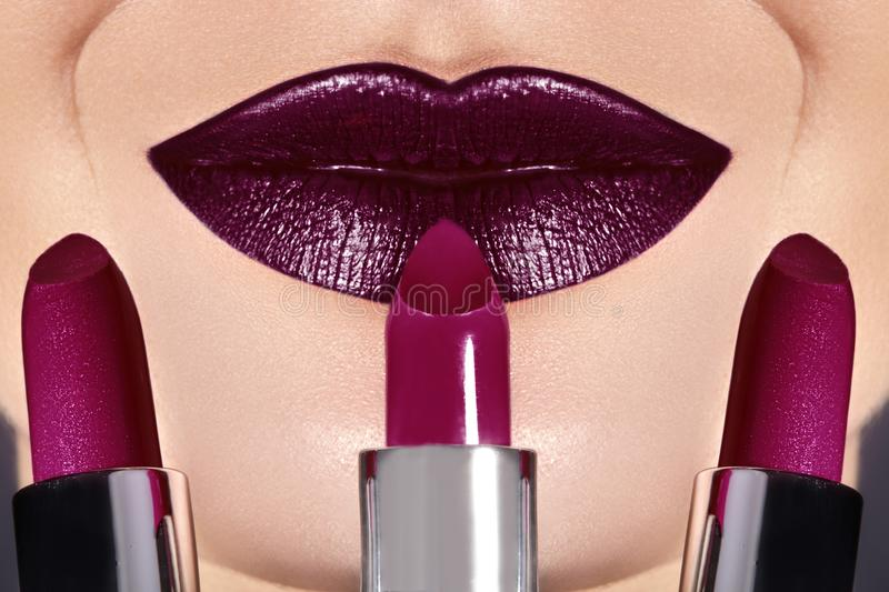 Trend Lips Makeup with bright dark Color Lipstick. Woman Applying Fashion lip Make-up. Choice lipstick. Close-up of woman`s lips with fashion dark make-up. Trend stock image