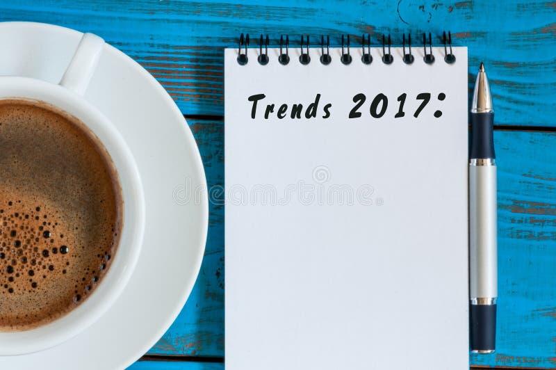 Trender 2017 som är skriftliga på notepaden på blått, bordlägger den near koppen för arbetsplatsen av morgonkaffe Affär och mode  royaltyfri fotografi