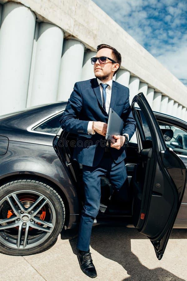 Trendig affärsman som kommer ut ur en bil royaltyfri foto