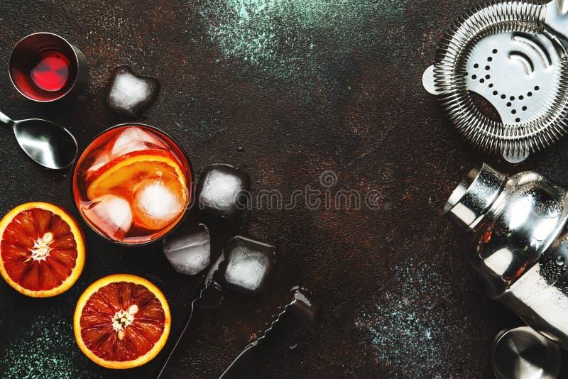 Trendig alkoholiserad coctail Negroni med torr gin, r?d vermut och r?da bitterhet-, apelsin- och iskuber Brun st?ngr?knare royaltyfri bild