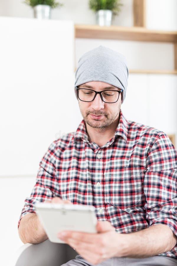 Trendig arkitekt eller utövande hållande minnestavlaapparat på hans kontor arkivbild