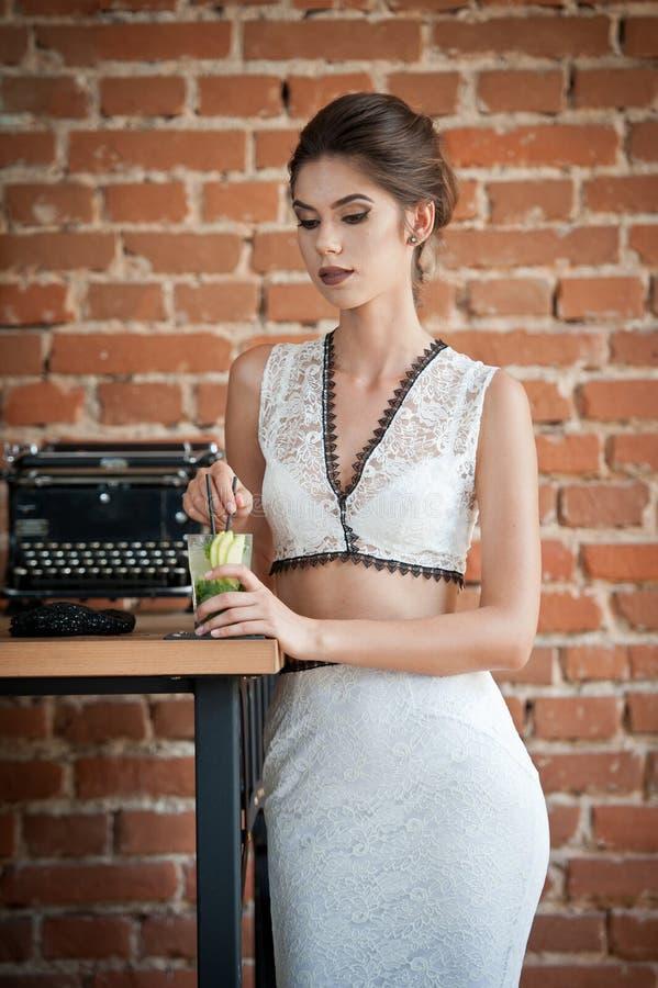 Trendig attraktiv dam med det vita klänninganseendet nära en restaurangtabell som har en drink kvinna för brunetthårkortslutning arkivfoton