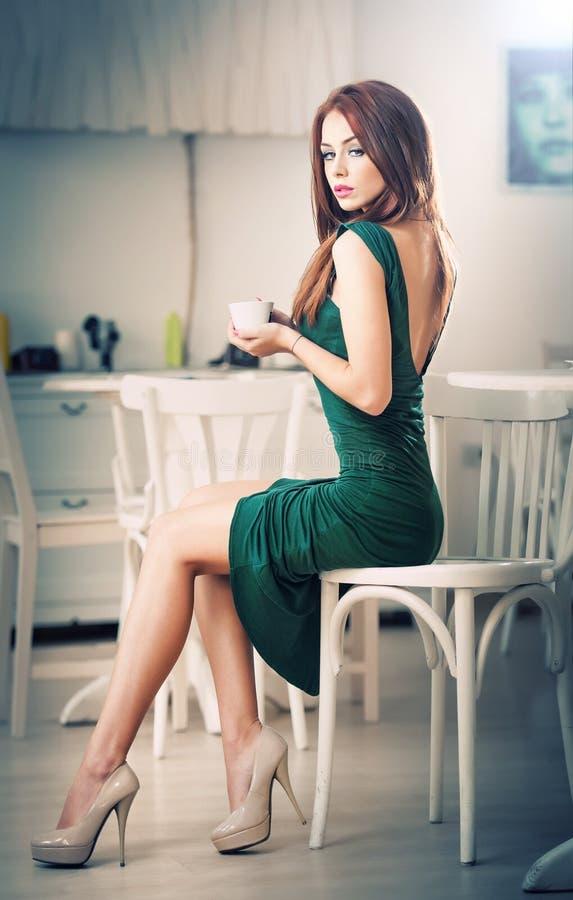 Trendig attraktiv ung kvinna i grönt klänningsammanträde i restaurang Härlig rödhårig man i elegant landskap med en kopp kaffe