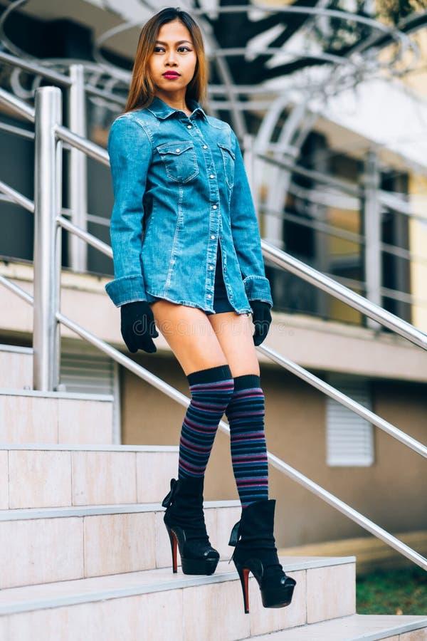 Trendig bärande jeans för ung kvinna klår upp med de höga kullarna och de långa bandknäsockorna Höstmodestil royaltyfria foton