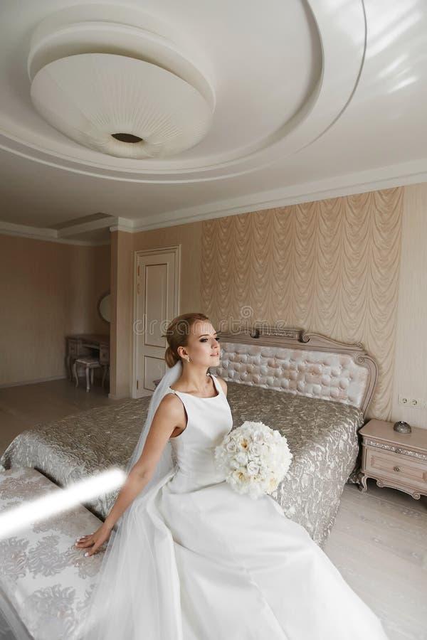 Trendig blond-haired ung kvinna med den stilfulla bröllopfrisyren och med ljus makeup, i en klänning för satängvit och med bouque arkivbilder