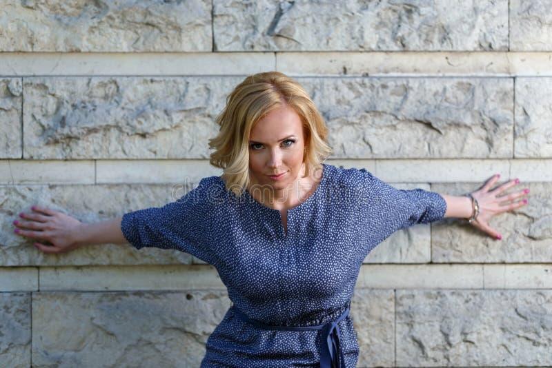 Trendig blond modell i aggressiv ställing nära stenväggen royaltyfria foton
