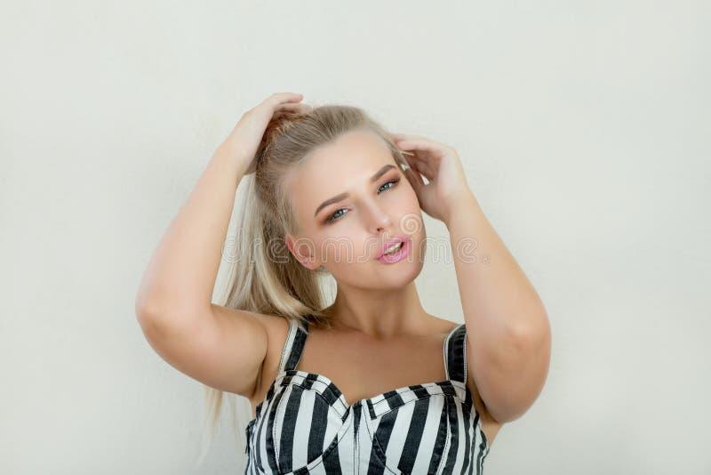 Trendig blond modell med rosa kanter och härliga blåa ögon royaltyfri fotografi