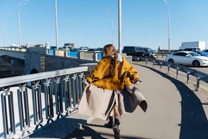 Trendig brunett som känner sig korsa fritt bron royaltyfri bild