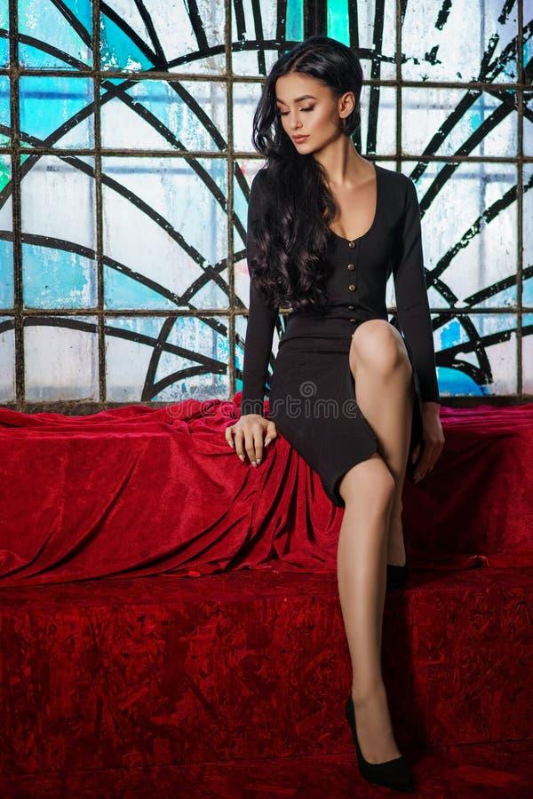 Trendig brunettkvinna i den svarta klänningen som sitter nära målat glassfönstret arkivfoton