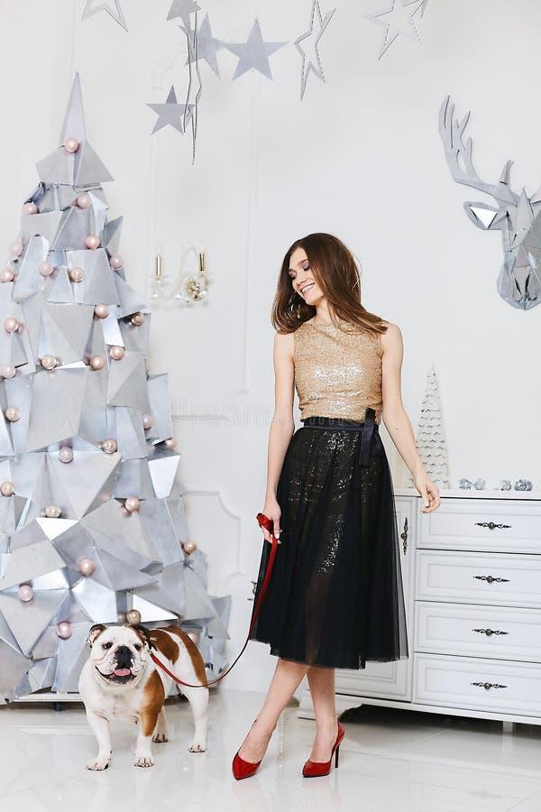 Trendig brunettmodellflicka i guld- blus, i en moderiktig svart kjol och i röda skor som poserar med den franska bulldoggen royaltyfri fotografi