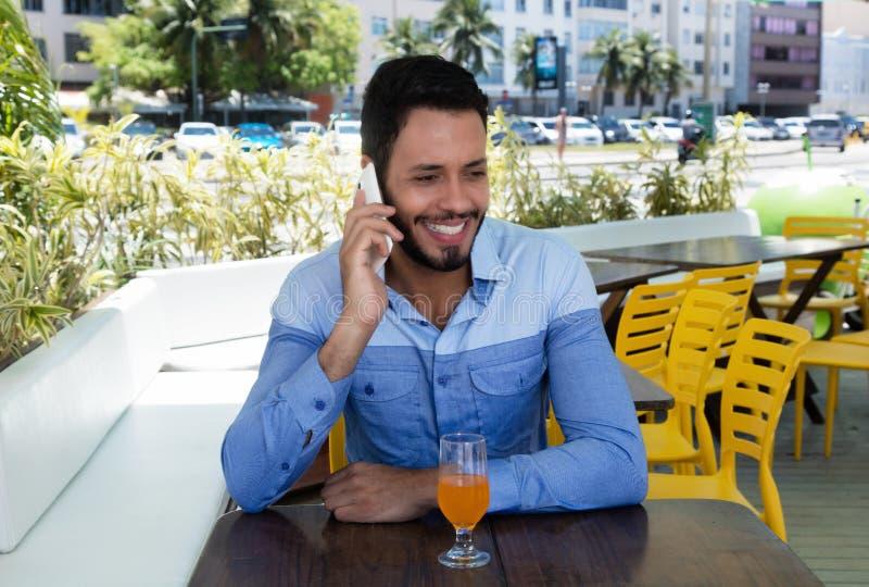 Trendig caucasian man som talar på telefonen i restaurang arkivbilder