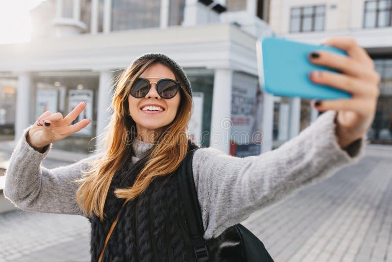 Trendig charmig härlig flicka i modern solglasögon, varm vintertröja som gör selfieståenden på gatan i stad royaltyfri fotografi