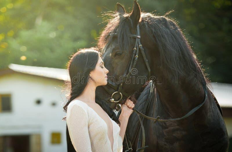 Trendig dam med den near bruna hästen för vit brud- klänning Härlig ung kvinna i en lång klänning som poserar med en vänlig häst royaltyfria bilder