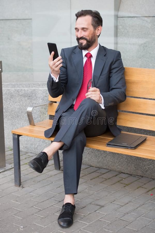 Trendig entrepren?r som anv?nder en smartphone, medan sitta p? b?nken med korsade ben royaltyfri bild