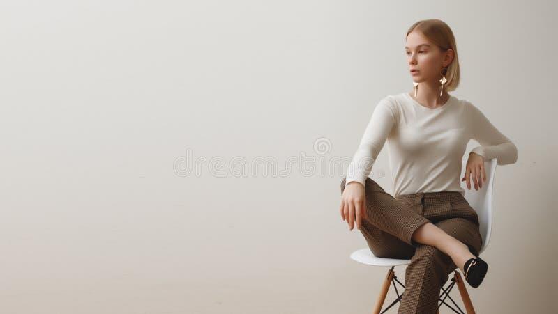 Trendig flicka i en vit tröja och rutiga flåsanden Naturlig livsstilstående av flickan, emotionellt och mode arkivbild