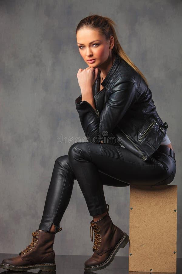 Trendig flicka i läder som poserar i studiobakgrund arkivfoto