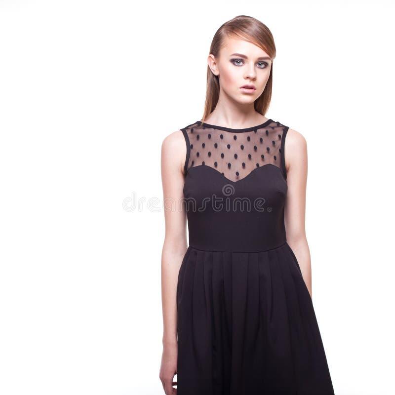 Trendig flicka i svart klänning på vit royaltyfri foto