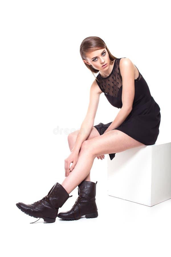 Trendig flicka i svart klänning på vit royaltyfri bild