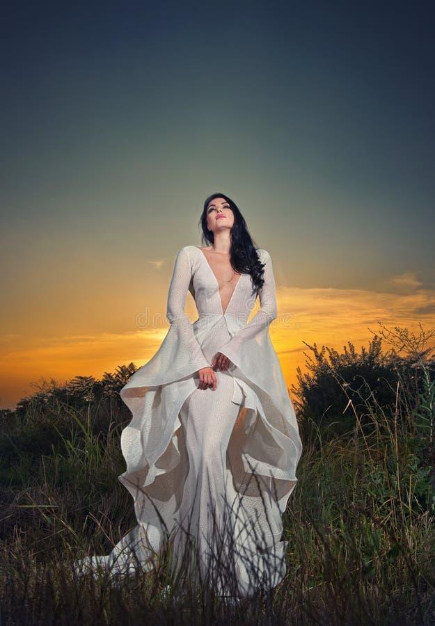Trendig härlig ung kvinna i vitt brud- långt posera för klänning som är utomhus- arkivbild