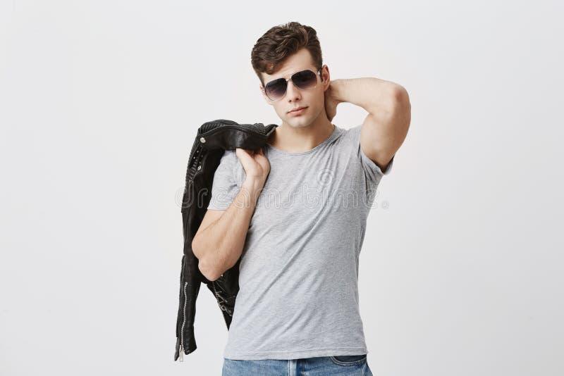 Trendig hipster med mörkt hår som poserar i den stilfulla eyewearen, tillfälligt klätt kastat svart läderomslag över hans fotografering för bildbyråer