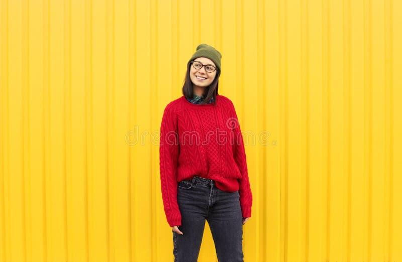 Trendig kläder för Millenial flicka som im har en bra tid som gör roliga framsidor nära den ljusa gula stads- väggen royaltyfria foton