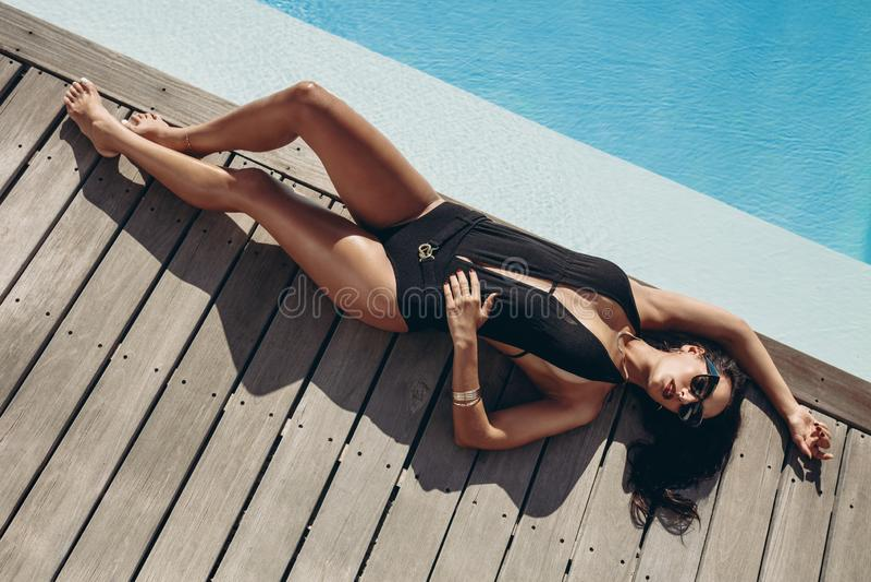 Trendig kvinna i bikini som solbadar poolsiden royaltyfria foton