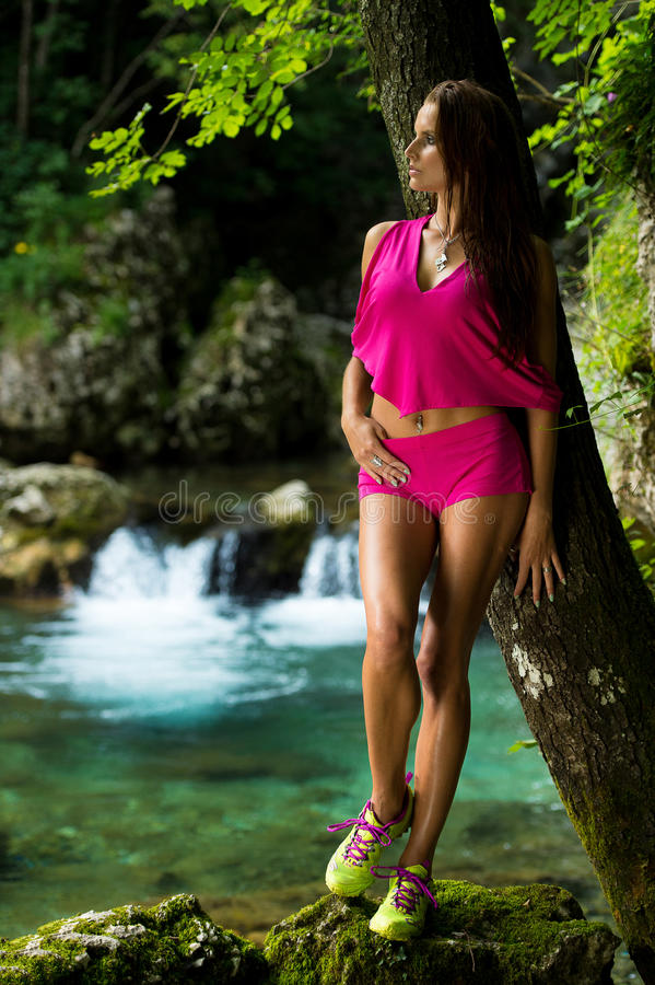 Trendig kvinna i mörk skog nära floden royaltyfria foton
