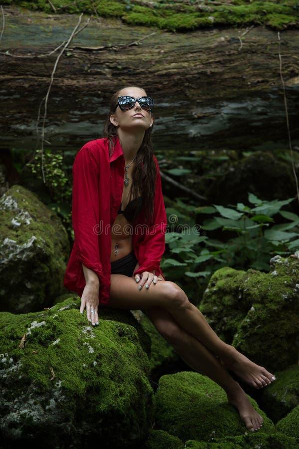 Trendig kvinna i mörk skog nära floden arkivbilder