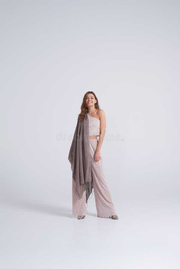 Trendig kvinna i moderiktiga kläder och halsduken som poserar i studio royaltyfri bild