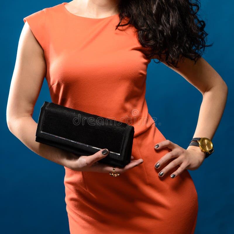 Trendig kvinna i röd aftonklänning med en svart handväska arkivfoto