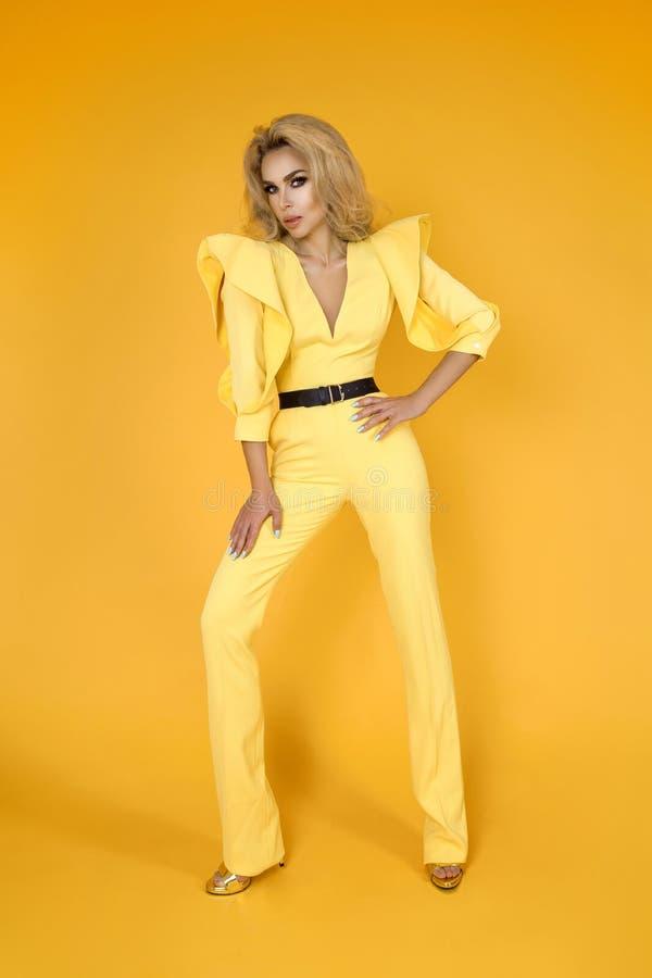Trendig kvinna i trevlig gul jumpsuit, skor och tillbehör Foto för modevårsommar - bild arkivbild