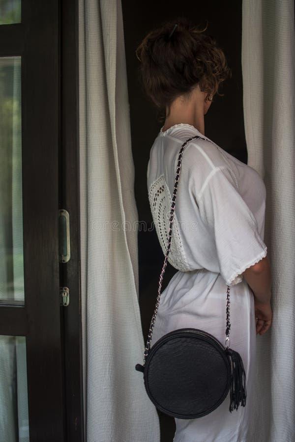 Trendig kvinna i vit udde med den svarta läderpåsen, tillbaka siktsbaksidasikt Närbild Elegant ung kvinna med den svarta läderpås royaltyfria foton