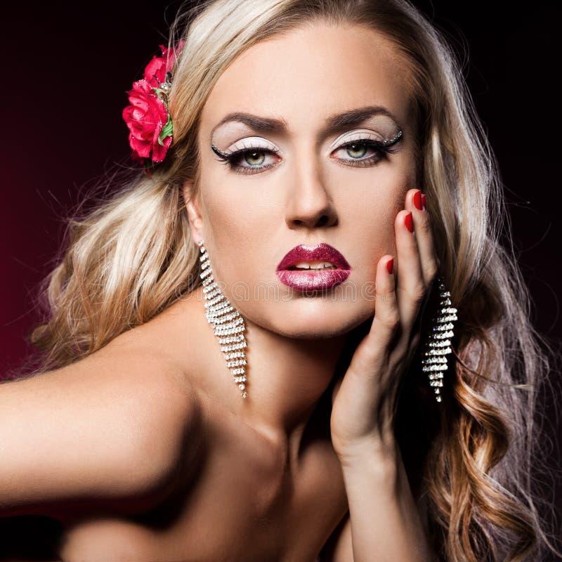 Trendig kvinna med blommor på hår royaltyfri fotografi