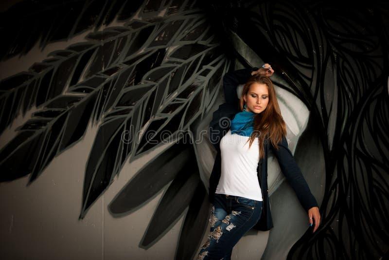 Trendig kvinna med blured graffitti i bakgrund royaltyfri fotografi