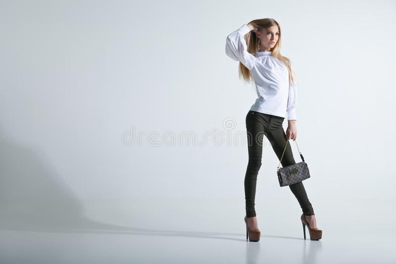 Trendig kvinna med en påse i ljus bakgrund royaltyfri fotografi