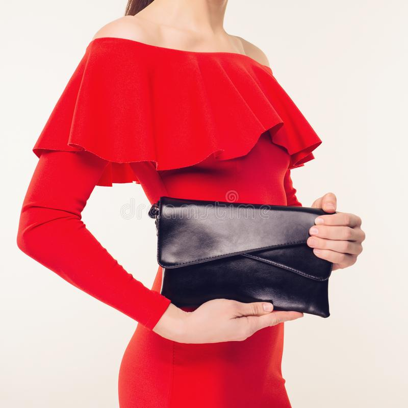 Trendig kvinna med en svart koppling i hennes händer och röda aftonklänning royaltyfria bilder