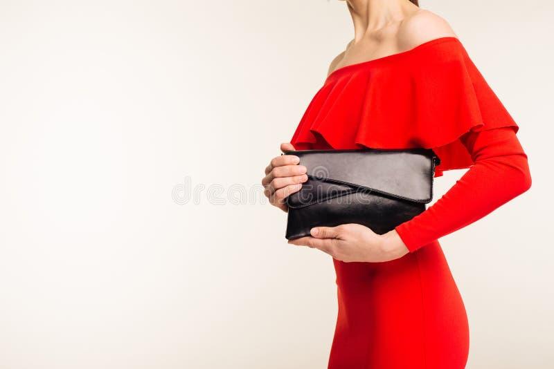 Trendig kvinna med en svart koppling i hennes händer och röda aftonklänning fotografering för bildbyråer