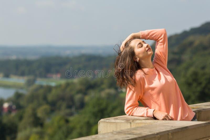 Trendig kvinna som utomhus poserar för fotografen royaltyfri foto