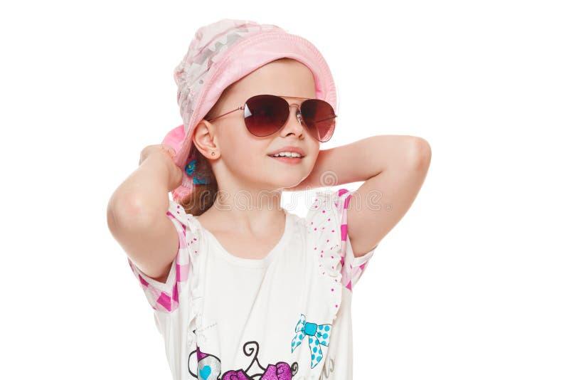 Trendig liten gullig flicka i solglasögon och hatten som isoleras på vit bakgrund arkivfoto