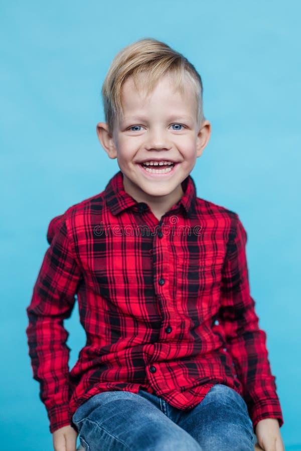 Trendig liten unge med den röda skjortan Mode stil Studiostående över blå bakgrund arkivbilder