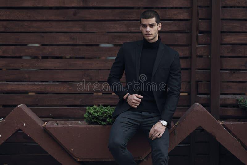 Trendig man och att bära en dräkt som sitter mot träväggen royaltyfri bild