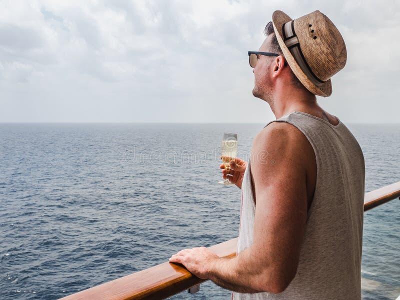 Trendig man som rymmer ett exponeringsglas av champagne arkivbild