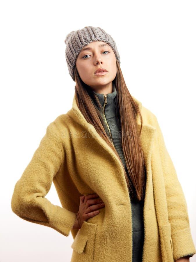 Trendig modell f?r hipsterbrunettkvinna i stilfull beige ?verrock och gr? hatt arkivbilder